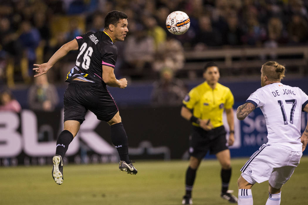 Julián Portugal (26) de Las Vegas Lights FC, se conecta con el balón durante un saque de esquina contra Marcel de Jong (17) del Vancouver Whitecaps FC en el partido de fútbol Cashman Field en L ...