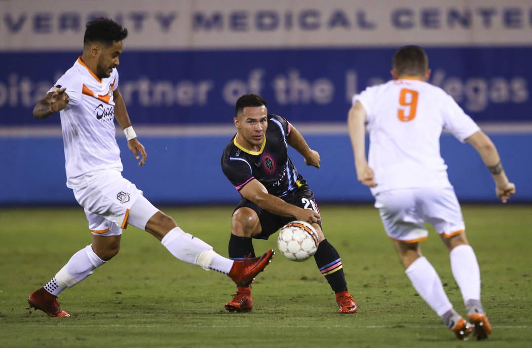 El centrocampista del Las Vegas Lights FC, Julian Portugal (26), pierde posesión del balón ante el delantero del Tulsa Roughnecks FC, Jhon Pirez, izquierda, y el centrocampista del Tulsa Roughne ...