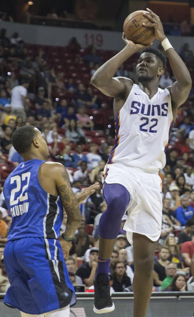 El centro de los Phoenix Suns, Deandre Ayton (22), tira sobre el guardia de Orlando Magic, Troy Caupain (22), en el segundo trimestre durante la Liga de verano de la NBA el lunes 9 de julio de 201 ...