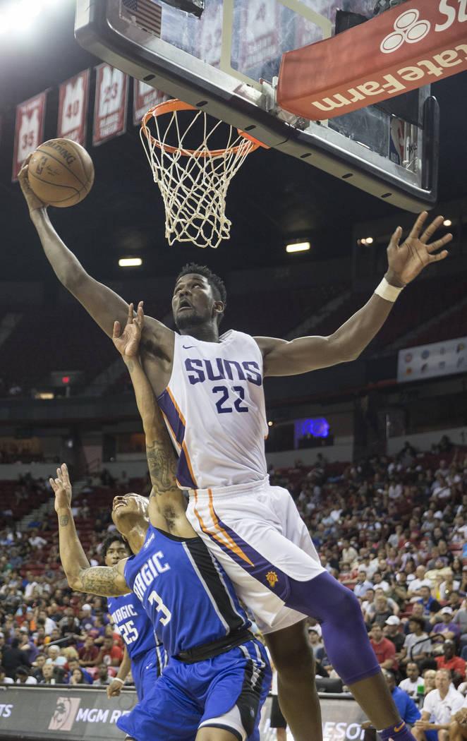 El centro De Phoenix Suns, Deandre Ayton (22), atrapa un rebote sobre el guardia de Orlando Magic, Jay Wright (3), en el tercer trimestre durante la Liga de verano de la NBA el lunes 9 de julio de ...