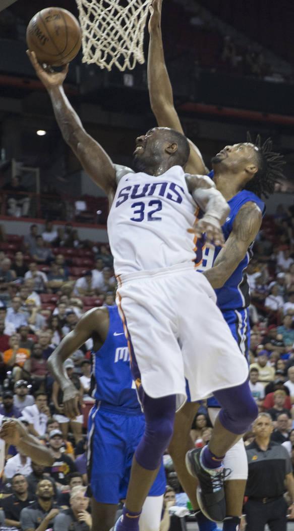 El escolta de los Suns de Phoenix, Davon Reed (32), pasa por encima del guardia de Orlando Magic, Braian Angola-Rodas (19), en el segundo trimestre durante la Liga de Verano de la NBA el lunes 9 d ...