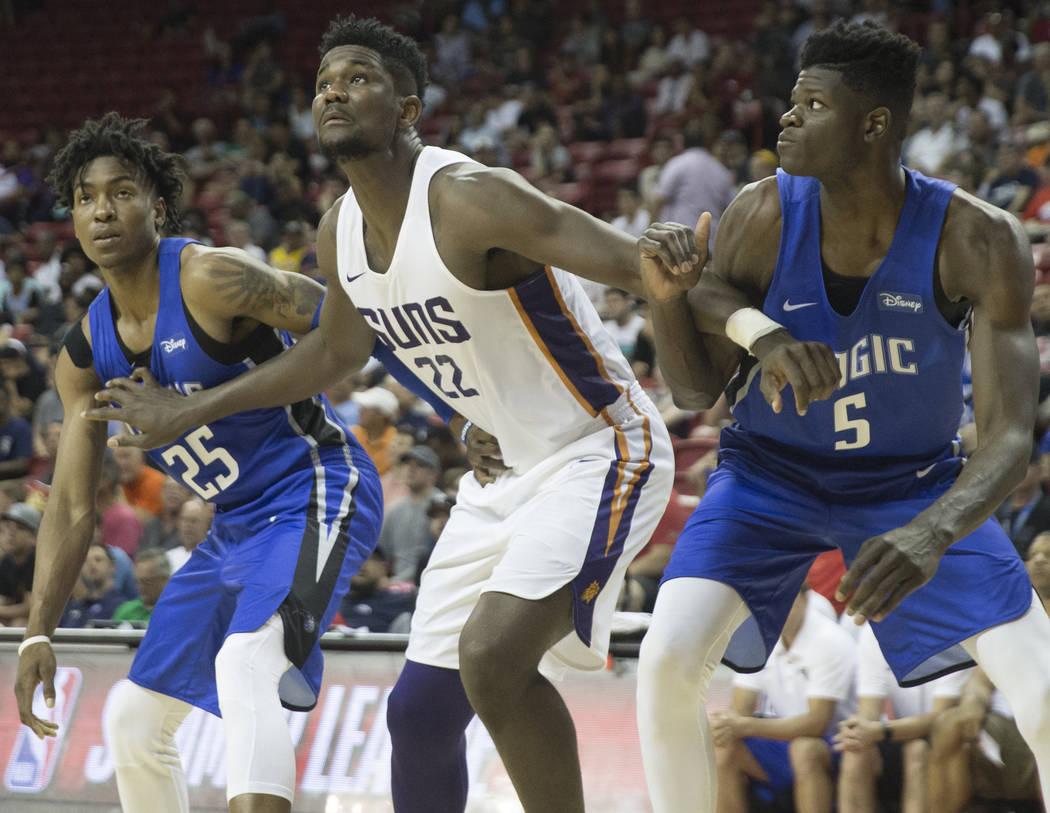 El centro de los Phoenix Suns, Deandre Ayton (22), lucha por un rebote con el alero de los Orlando Magics, Wesley Iwundu (25), y el centro Mohamed Bamba (5) en el tercer cuarto durante la NBA Summ ...