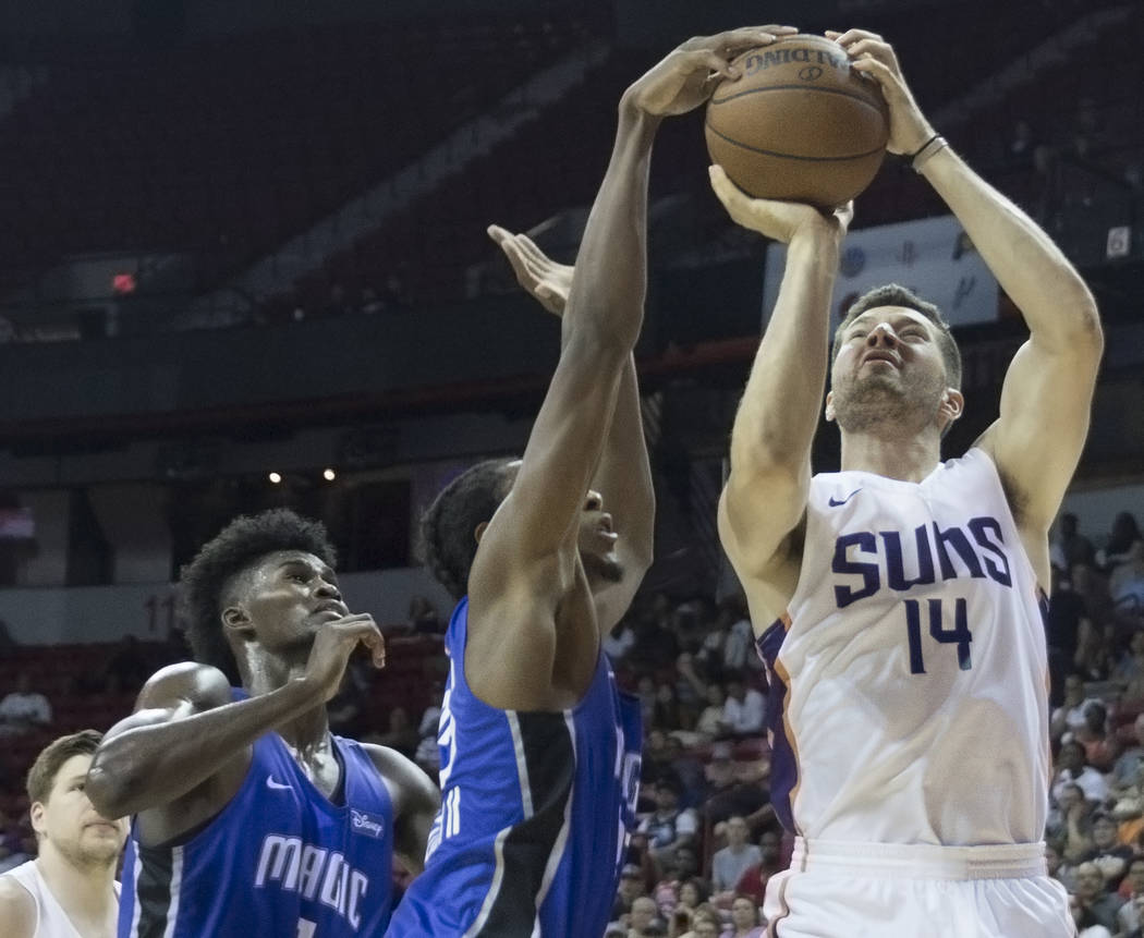 El alero de los Phoenix Suns, Alec Peters (14), recibe su tiro bloqueado por el guardia de Orlando Magic, Melvin Frazier Jr. (35), en el tercer cuarto durante la NBA Summer League el lunes 9 de ju ...