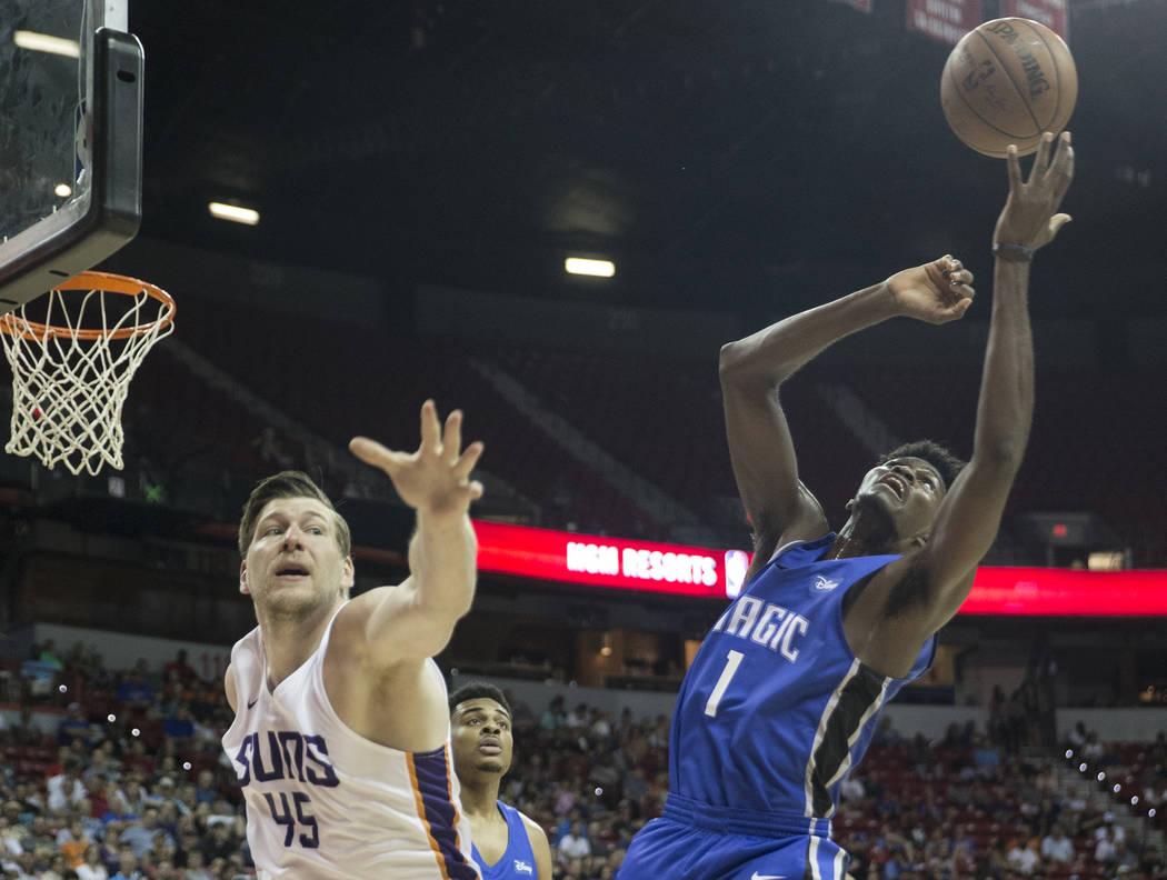 El centro de los Phoenix Suns Jack Cooley (45) y el alero del Orlando Magic, Jonathan Isaac (1) buscan un balón suelto en el tercer cuarto durante la NBA Summer League el lunes 9 de julio de 2018 ...