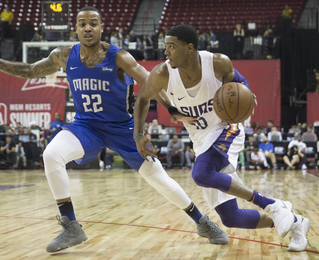 El guardia de los Phoenix Suns Shaquille Harrison (10) supera a Troy Caupain (22) de los Orlando Magics en el segundo trimestre durante la NBA Summer League el lunes 9 de julio de 2018 en el Thoma ...