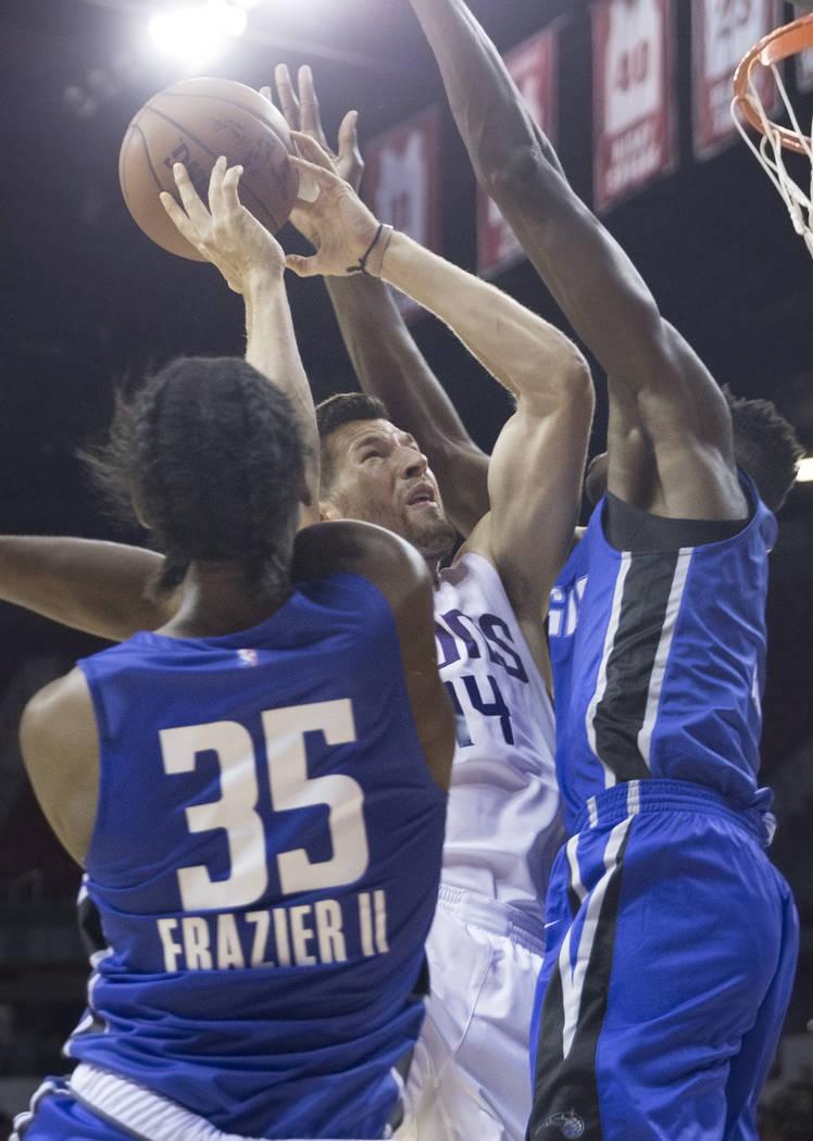 El alero de los Phoenix Suns, Alec Peters (14), pasa por delante del guardameta de los Orlando Magics, Melvin Frazier Jr. (35), y del pívot Mohamed Bamba (5) en el tercer cuarto durante la NBA Su ...