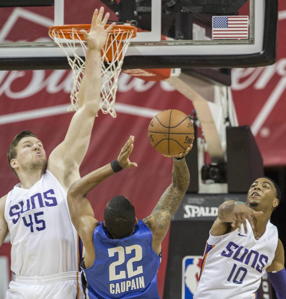 El centro de los Phoenix Suns, Jack Cooley (45), y el guardia Shaquille Harrison (10), saltan para bloquear el tiro del guardia de Orlando Magic, Troy Caupain (22), en el primer cuarto durante la ...