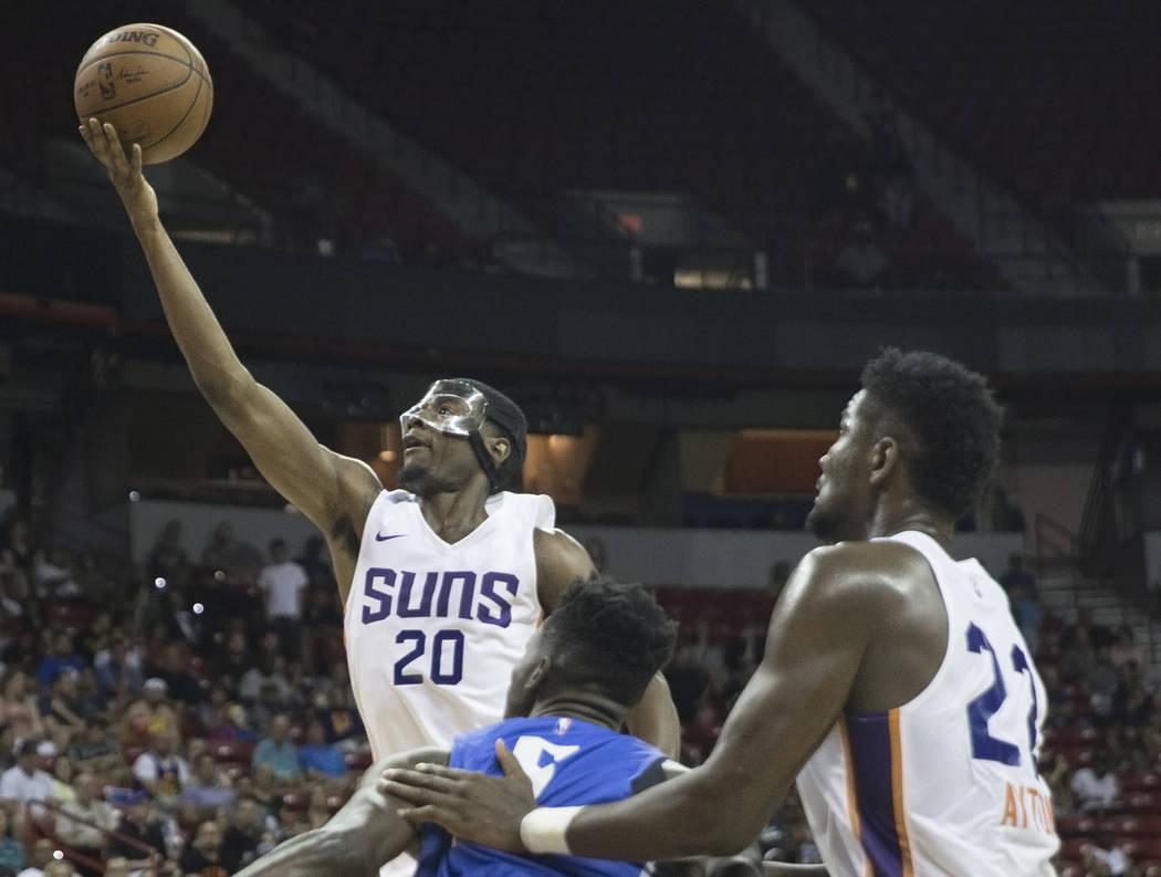 El alero de los Phoenix Suns, Josh Jackson (20), pasa por el centro de Orlando Magic, Mohamed Bamba (5), en el segundo trimestre durante la Liga de verano de la NBA el lunes 9 de julio de 2018 en ...