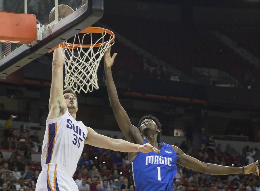 El alero de los Phoenix Suns, Dragan Bender (35), supera al alero del Orlando Magic, Jonathan Isaac (1) en el segundo trimestre durante la Liga de verano de la NBA el lunes 9 de julio de 2018 en e ...