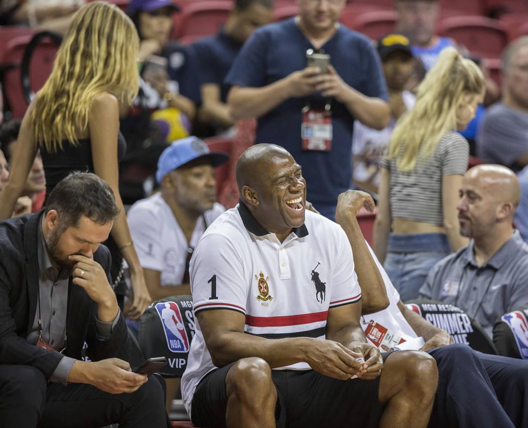 El ex jugador de los Lakers y actual gerente general, Magic Johnson, comparte una sonrisa con sus amigos durante el juego de la NBA Summer League de Los Ángeles con los New York Knicks el martes ...