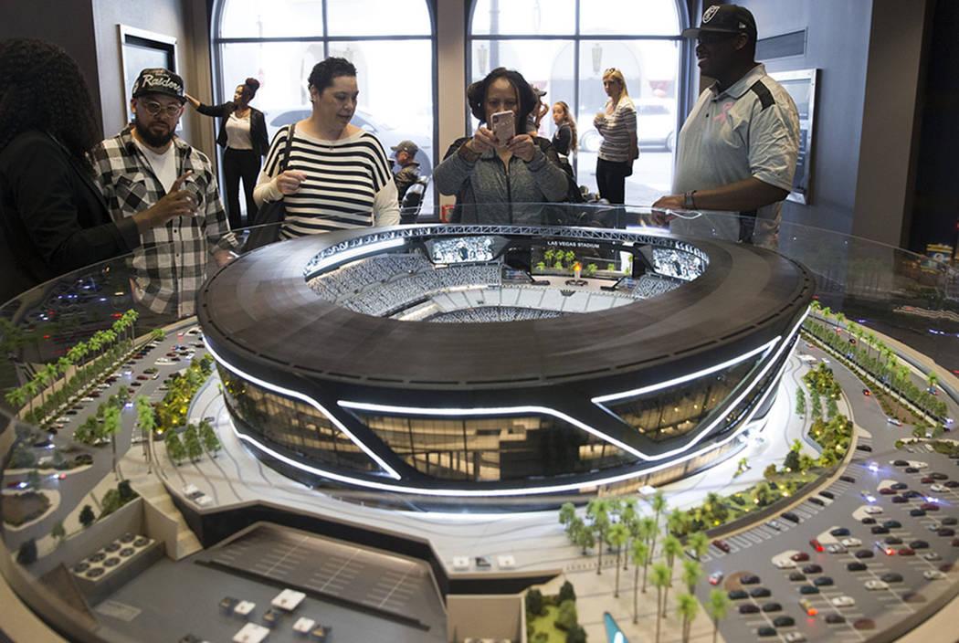 Kaipo Dean, desde la izquierda, su hermana Chianti Lloyd, su madre Roxy Dean y su cuñado, Dewan Lloyd, ven el modelo de un estadio Raiders expuesto en el centro de pruebas del estadio de Las Vega ...