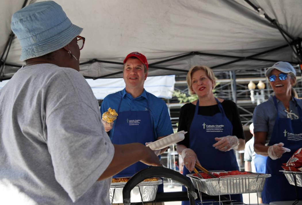 El candidato a la Corte Suprema, Brett Kavanaugh, segundo desde la izquierda, sirve macarrones y queso a las personas sin hogar mientras se ofrece como voluntario en Catholic Charities, el miérco ...