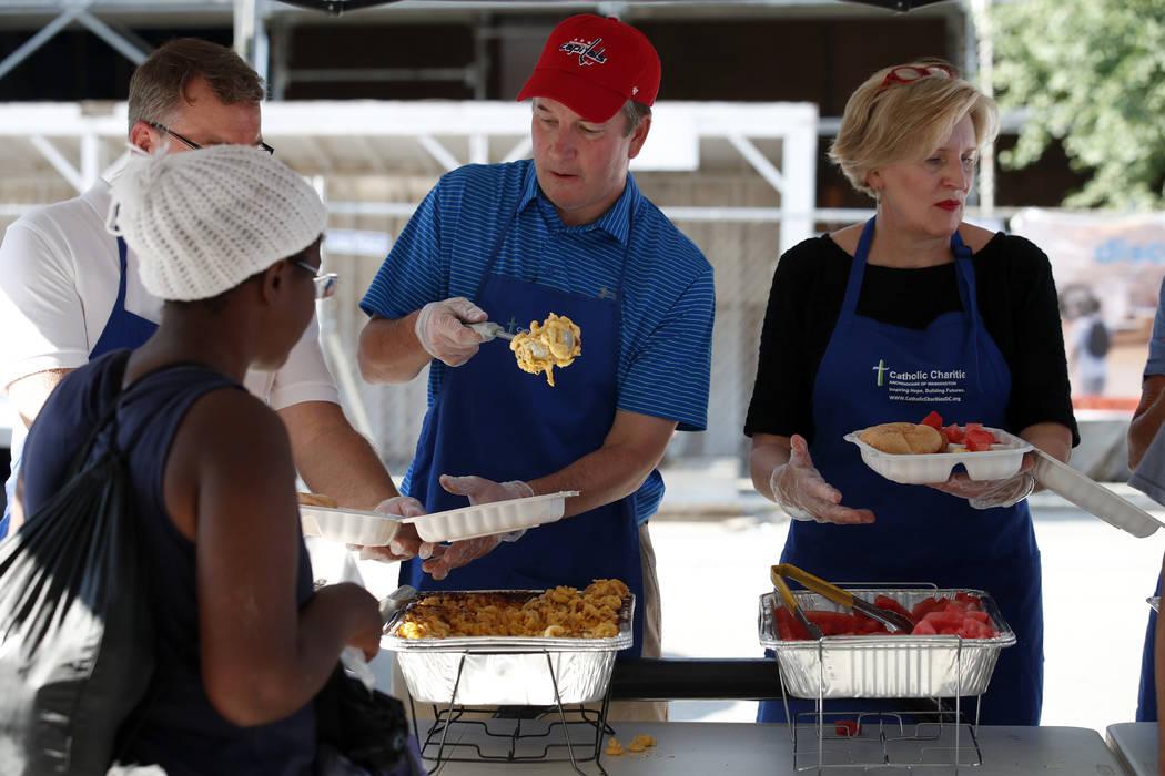 El candidato a la Corte Suprema, Brett Kavanaugh, en el centro, sirve macarrones con queso a las personas sin hogar mientras trabaja como voluntario en Catholic Charities, el miércoles 11 de juli ...