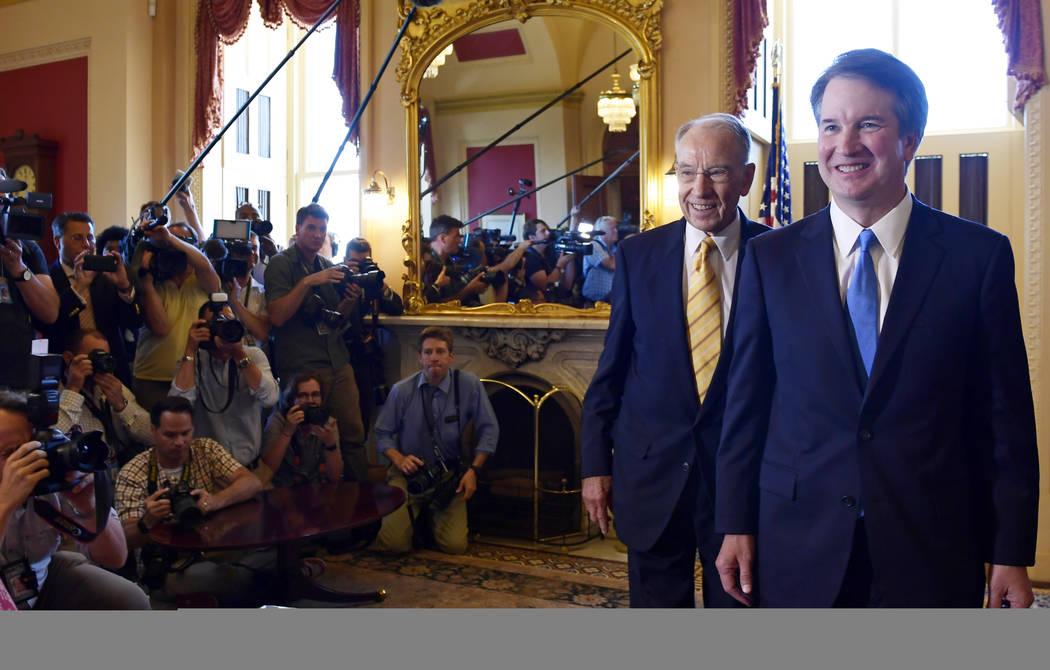 El candidato a la Corte Suprema, Brett Kavanaugh, derecha, y el senador Chuck Grassley, R-Iowa, segundo desde la derecha, pasan frente a la prensa después de una foto en Capitol Hill, Washington, ...