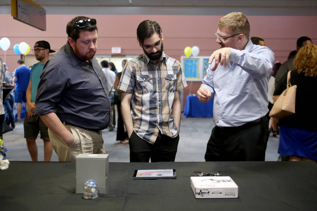 David Clark, izquierda, y Roger Cruz escuchan a Joerg Radler, un ingeniero de Apple, en College of Southern Nevada en Las Vegas, el jueves 12 de julio de 2018. Radler explicó cómo los estudiante ...