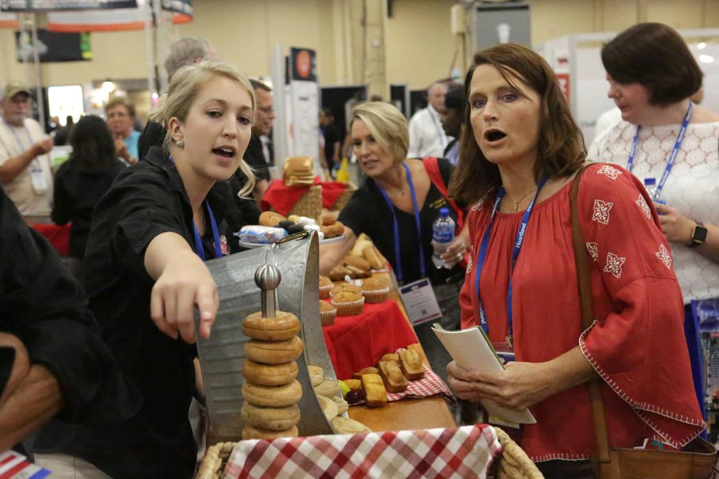 Christine Collins de la Bake Crafters Food Company, señala productos a Lory Hayon, dietista registrada del Distrito Escolar del Condado de Clark, durante la conferencia anual de la Asociación de ...