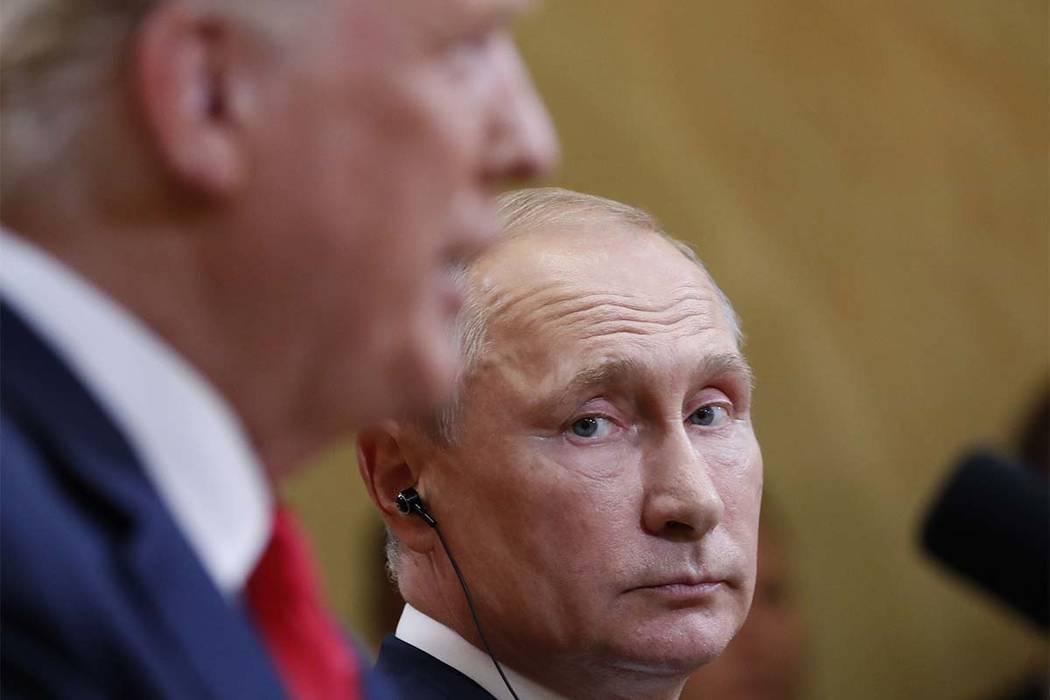 El presidente ruso, Vladimir Putin, escucha al presidente Donald Trump durante una conferencia de prensa después de que ambos se reunieron en el Palacio Presidencial en Helsinki, Finlandia, el lu ...