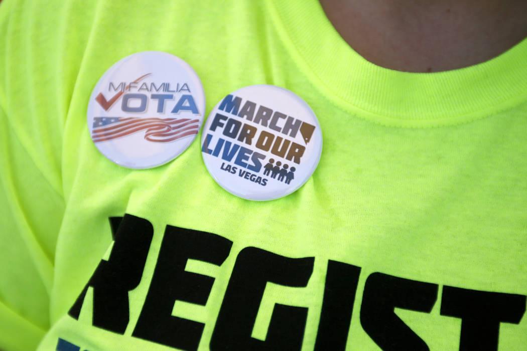 Kaitlyn Willoughby muestra sus botones en un Road to Change Voter Registration Walk en Sunset Park en Las Vegas, el lunes 16 de julio de 2018. El evento fue organizado por el grupo March for Our L ...