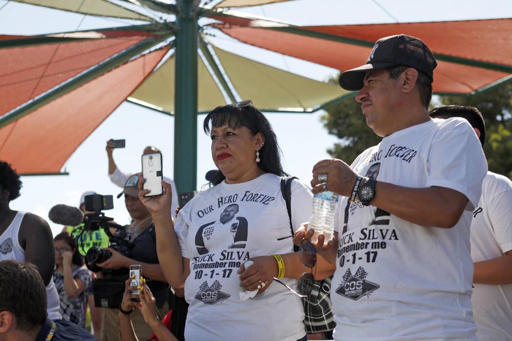 Angélica Cervantes, izquierda, y su esposo Gregorio De La Rosa miran cómo Manny Oliver crea un mural en una Caminata de Registro de Votantes de Road to Change en Sunset Park en Las Vegas, el lun ...