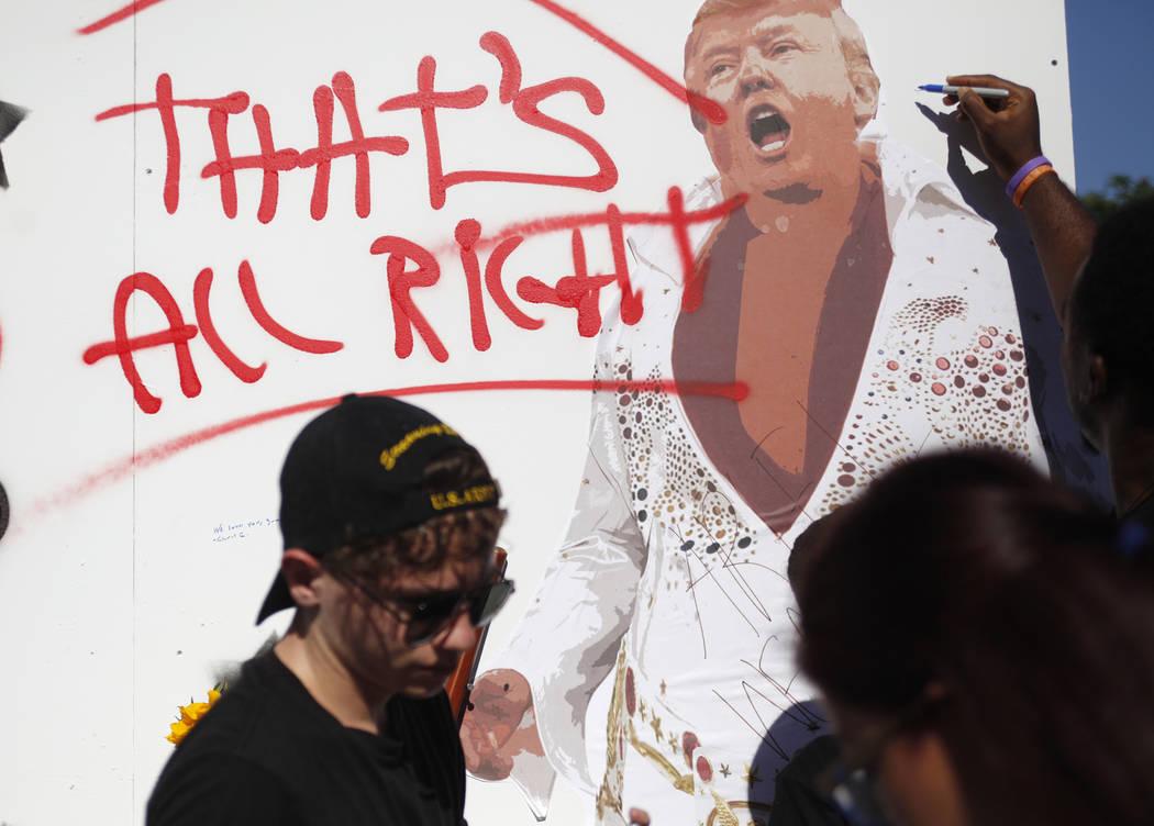 Las personas firman un mural realizado por Manny Oliver en un Road to Change Voter Registration Walk en Sunset Park en Las Vegas, el lunes 16 de julio de 2018. El evento fue organizado por el grup ...