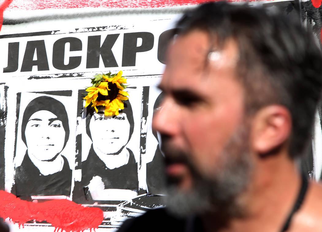 Manny Oliver, detrás de él imágenes de su hijo, se dirige a la multitud después de pintar un mural en una Caminata de Registro de Votantes de Road to Change en Sunset Park en Las Vegas, el lun ...
