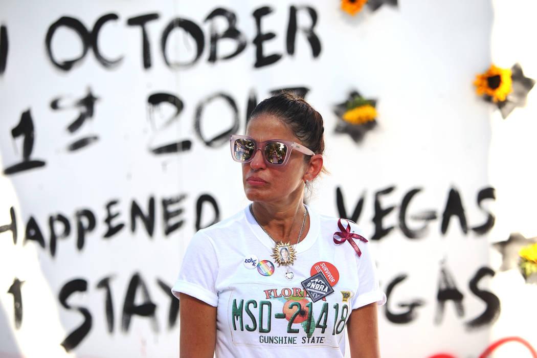 Patricia Oliver escucha a su esposo Manny Oliver dirigirse a la multitud después de pintar un mural en una Caminata de Registro de Votantes de Road to Change en Sunset Park en Las Vegas, el lunes ...