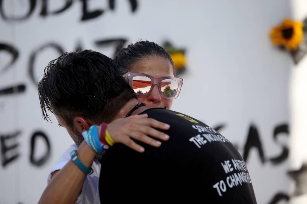 Patricia Oliver abraza a su esposo Manny Oliver después de pintar un mural en una Caminata de Registro de Votantes de Road to Change en Sunset Park en Las Vegas, el lunes 16 de julio de 2018. El ...