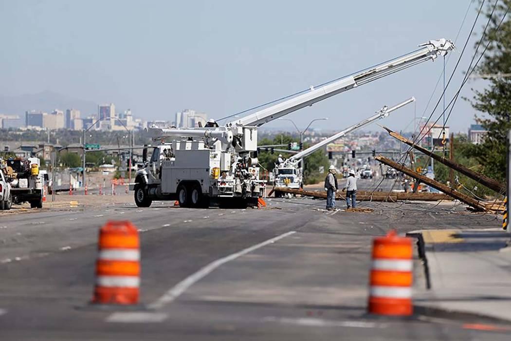 Las cuadrillas de NV Energy trabajan para reparar las líneas eléctricas dañadas por una tormenta eléctrica a última hora de la noche en Boulder Highway, cerca de Sunset Road. (Max Michor / La ...
