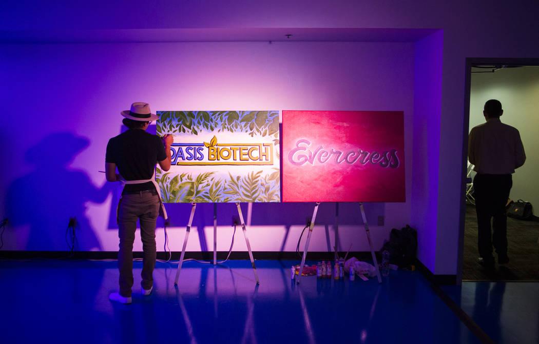 Jeremiah Kaniaupio, izquierda, pinta el logotipo de Oasis Biotech durante un gran evento de inauguración de la empresa agrícola de interior en Las Vegas el miércoles 18 de julio de 2018. Chase ...