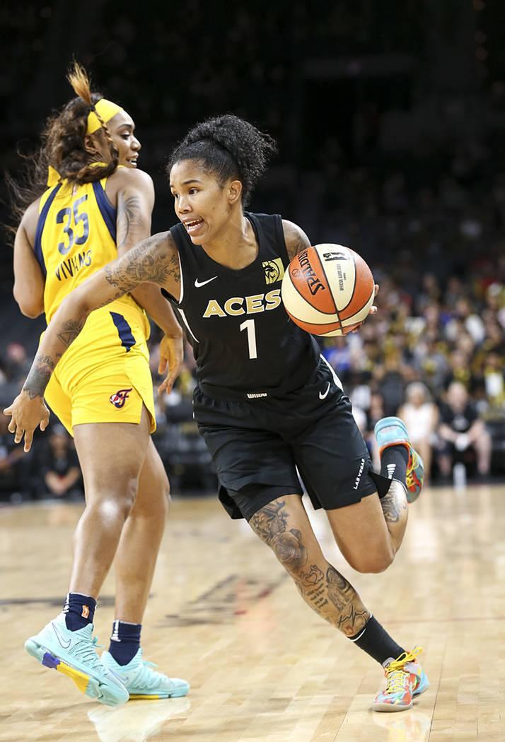 La jugadora de Las Vegas Aces, Tamera Young (1), conduce el balón ante la marca de la jugadora de Indiana Fever, Victoria Vivians (35), durante la segunda mitad de un partido de baloncesto de la ...