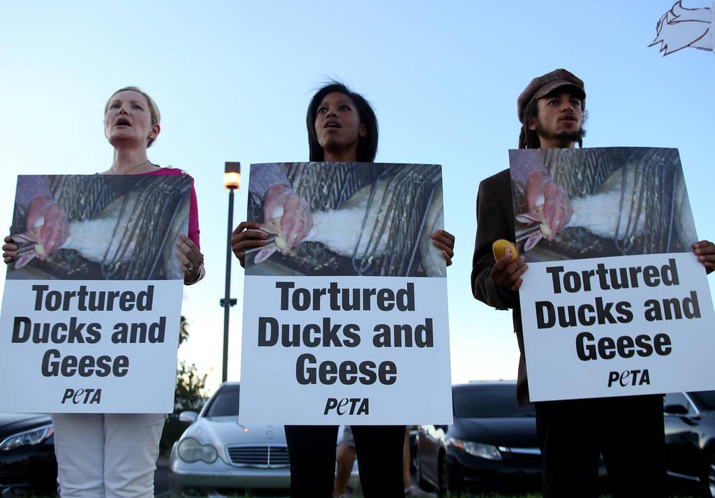 Sarika Goode, desde la izquierda, Valerie Worthen, y Anthony Murie, de Animal Action Las Vegas, un grupo vegano, protestan contra las prácticas de Sparrow + Wolf en Las Vegas, el domingo 22 de ju ...