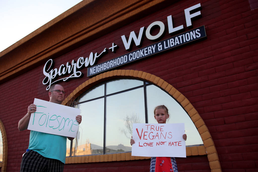 Alan Frederick, izquierda, y su hija, Ella Frederick, de 7 años, muestran su apoyo a Sparrow + Wolf mientras el grupo vegano Animal Action Las Vegas protesta por las prácticas del restaurante en ...