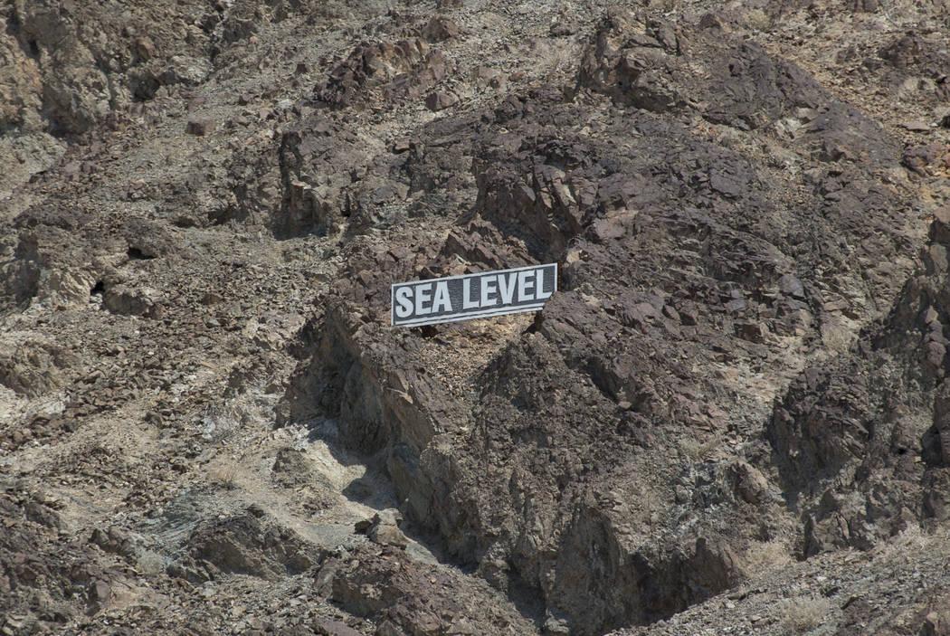 Un letrero que marca el nivel del mar se encuentra en el acantilado de Badwater Basin, a 282 pies bajo el nivel del mar, en el Parque Nacional Death Valley, California, el jueves 26 de julio de 20 ...