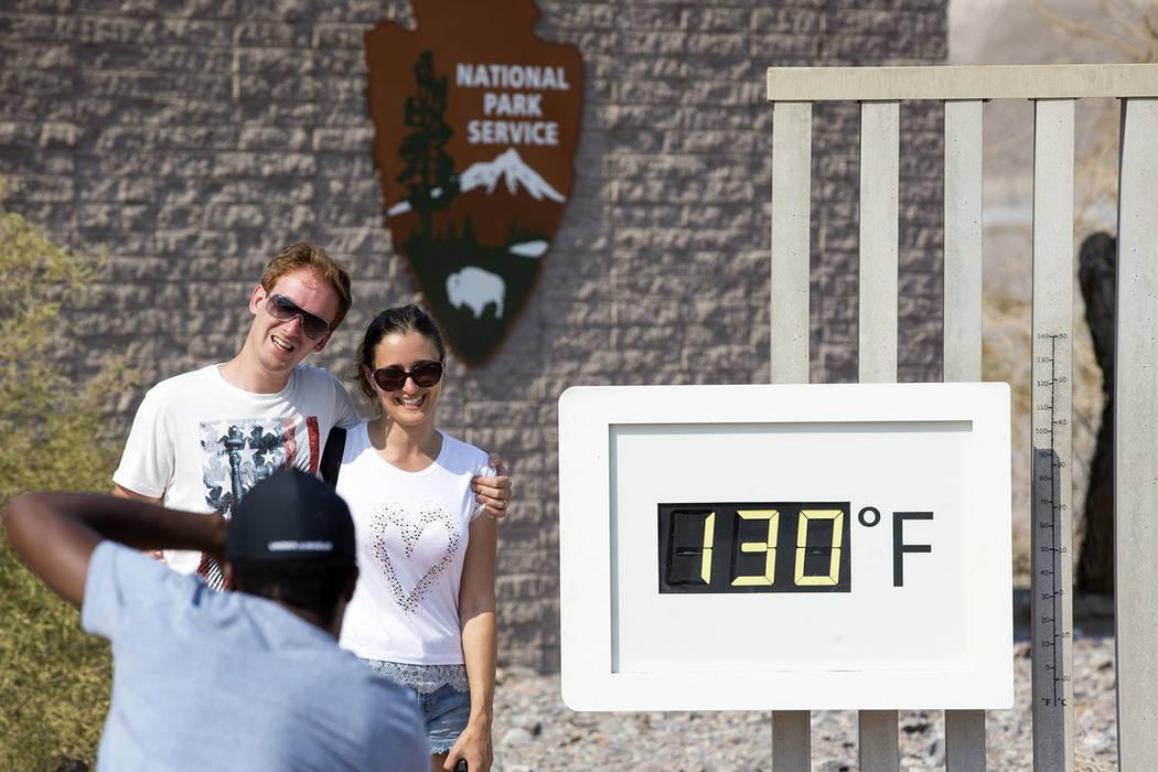 Una pareja posa en el termómetro Furnace Creek Visitor Center en el Parque Nacional Death Valley, California, el jueves 26 de julio de 2018. La temperatura oficial en el parque aumentó a 127 el ...