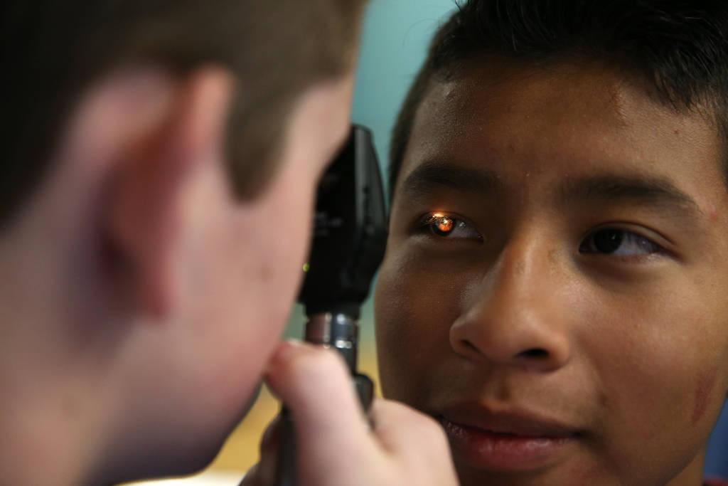 Andrew Hawkins, a la izquierda, 14, revisa el ojo de Gunner Negrete, 14, durante CampMED en UNLV en Las Vegas, el viernes 20 de julio de 2018. En CampMED, los estudiantes interesados en el campo d ...