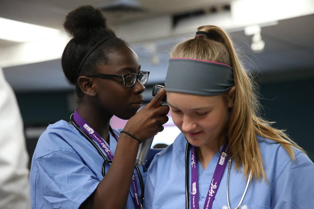 Damera Spann, izquierda, 14, revisa la oreja de Halsey Hughes, 14, durante CampMED en UNLV en Las Vegas, el viernes 20 de julio de 2018. En CampMED, los estudiantes interesados en el campo de la m ...