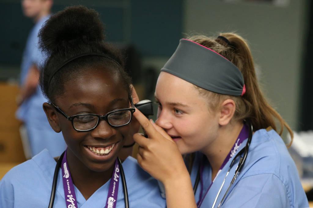 Halsey Hughes, derecha, 14, revisa la oreja de Damera Spann, 14, durante CampMED en UNLV en Las Vegas, el viernes 20 de julio de 2018. En CampMED, los estudiantes interesados en el campo de la med ...
