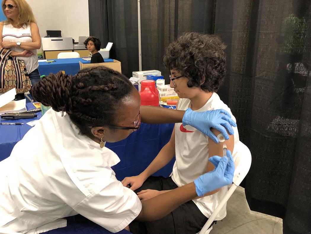 El niño Matt Feris, de 12 años, es vacunado con el copatrocinio de Walmart Pharmacy, en la Feria de Regreso a Clases. En The Boulevard, el 28 de julio de 2018. Foto Valdemar González / El Tiemp ...
