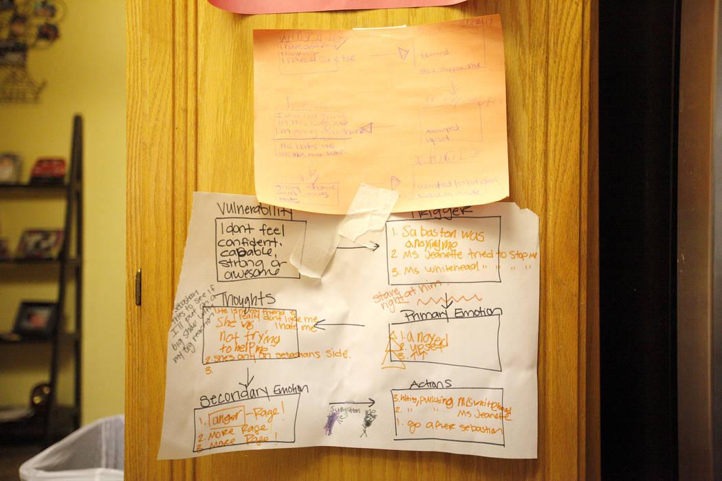 Carrie Olsen señala una tabla que ayuda a su hijo Daemion Olsen, de 9 años, a entender mejor su salud mental en su casa de Las Vegas, el martes 31 de julio de 2018. Medicaid anunció una nueva r ...