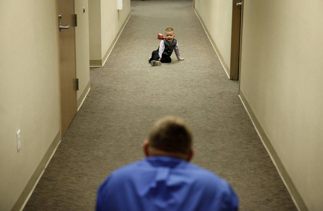 Daemion Olsen, de tres años, juega con su padre Jeff Olsen, abajo, en un pasillo del Centro de Tribunales y Servicios Familiares de Las Vegas, el martes 13 de marzo de 2012. Jeff Olsen y su espos ...