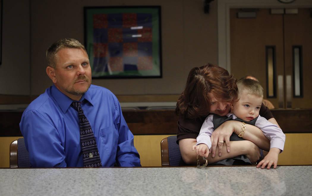 Daemion Olsen, de tres años, es abrazado por su madre Carrie Olsen mientras Jeff Olsen se sienta a su lado durante una audiencia de adopción en el Centro de Tribunales y Servicios Familiares en ...