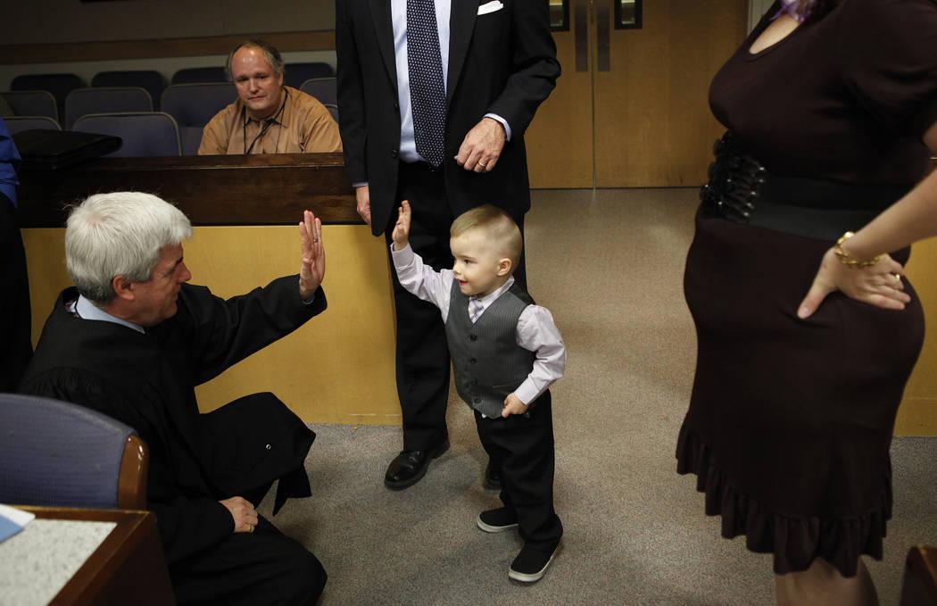 Daemion Olsen, de 3 años, centro, le da la mano al Juez Frank P. Sullivan después de una audiencia de adopción en el Centro de Tribunales y Servicios Familiares en Las Vegas el martes 13 de mar ...