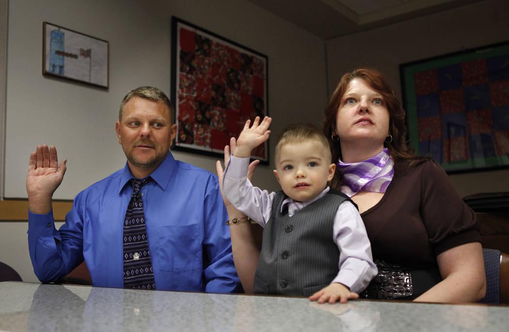 Daemion Olsen, de tres años, imita a su madre, Carrie Olsen, a la derecha, y al padre, Jeff Olsen, cuando prestaron juramento durante una audiencia de adopción en el Centro de Tribunales y Servi ...