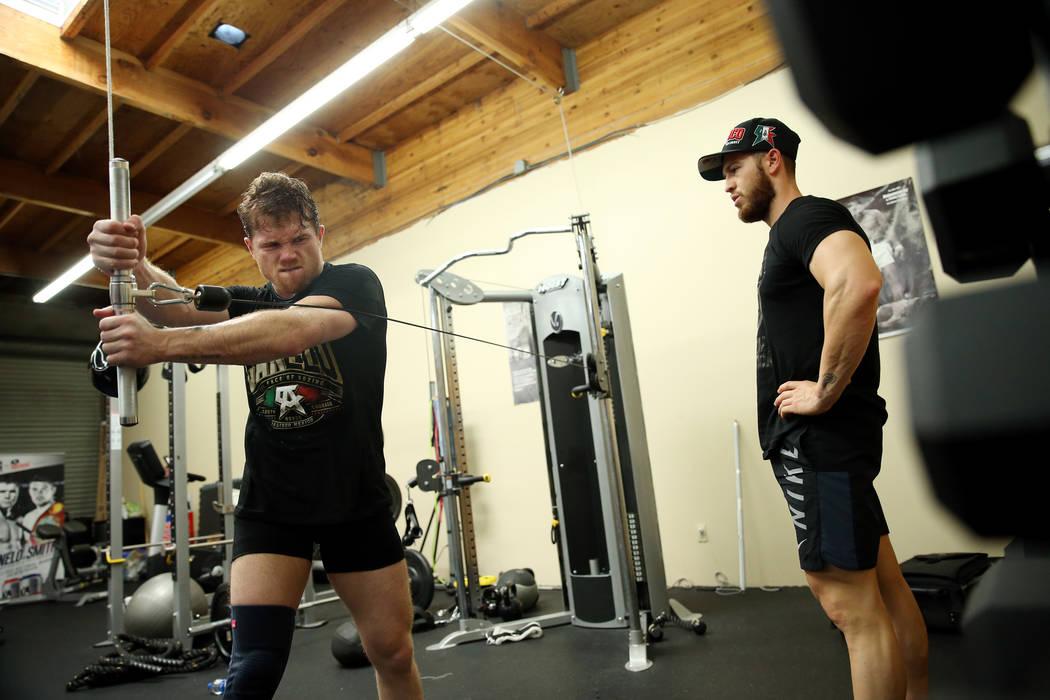"""El boxeador Saúl """"Canelo"""" Álvarez, a la izquierda, trabaja con su entrenador Raúl Arreola en su gimnasio en San Diego, California, el viernes 27 de julio de 2018. Erik Verduzco Las Vegas Review ..."""
