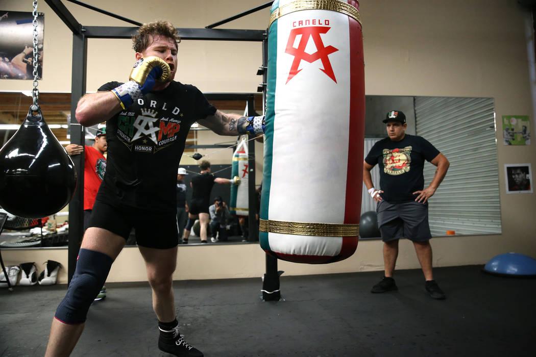 """Saúl """"Canelo"""" Álvarez, a la izquierda, golpea la bolsa mientras su entrenador Eddy Reynoso lo observa durante un entrenamiento en su gimnasio en San Diego, California, el viernes 27 de julio de ..."""