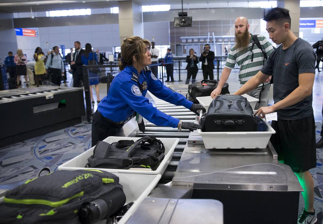 La agente de la Administración de Seguridad del Transporte, Donna Franco, izquierda, asiste a un pasajero en una de las nuevas vías automatizadas de detección en la Terminal 3 del Aeropuerto In ...