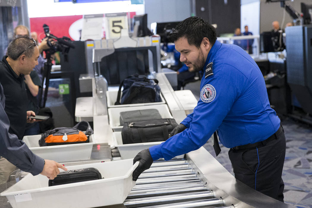 El agente de la Administración de Seguridad del Transporte Eduardo Puga, a la derecha, asiste a un pasajero en una de las nuevas vías automatizadas de detección en la Terminal 3 del Aeropuerto ...