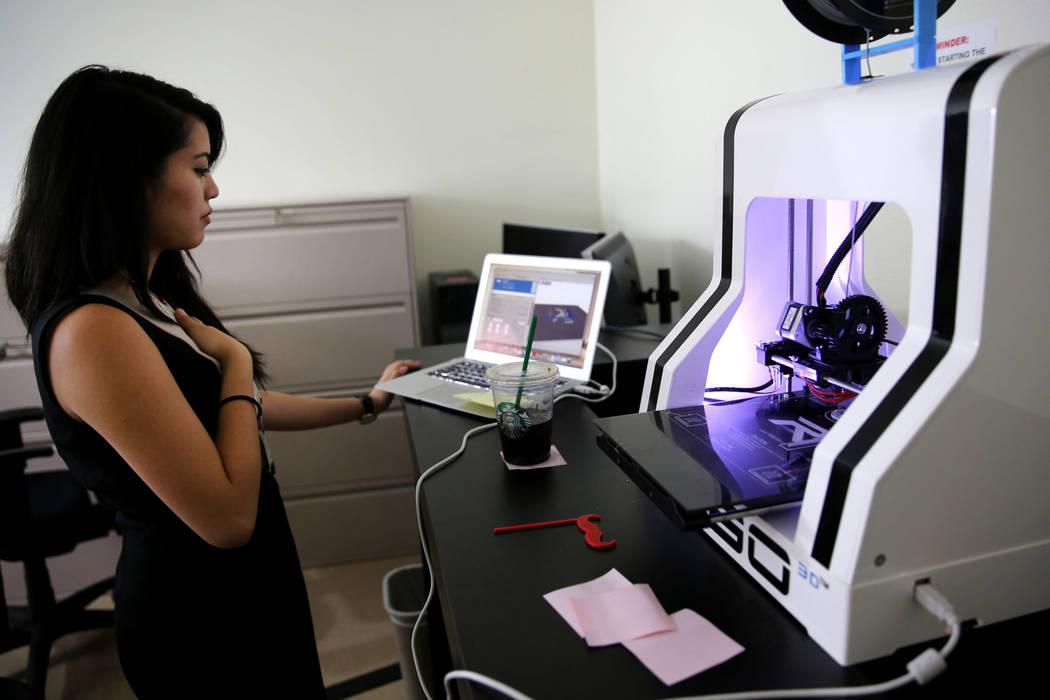 Talitha La Putt, y pasante del Centro de Desarrollo de Pequeñas Empresas, demuestra una impresora 3D durante la jornada de puertas abiertas para Nevada Business Development Services ubicada en la ...