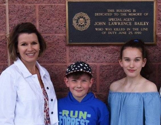 Una foto de la hija del agente especial John Bailey y sus nietos frente al edificio del FBI en Las Vegas, que fue nombrado en su honor. (Oficina Federal de Investigaciones)