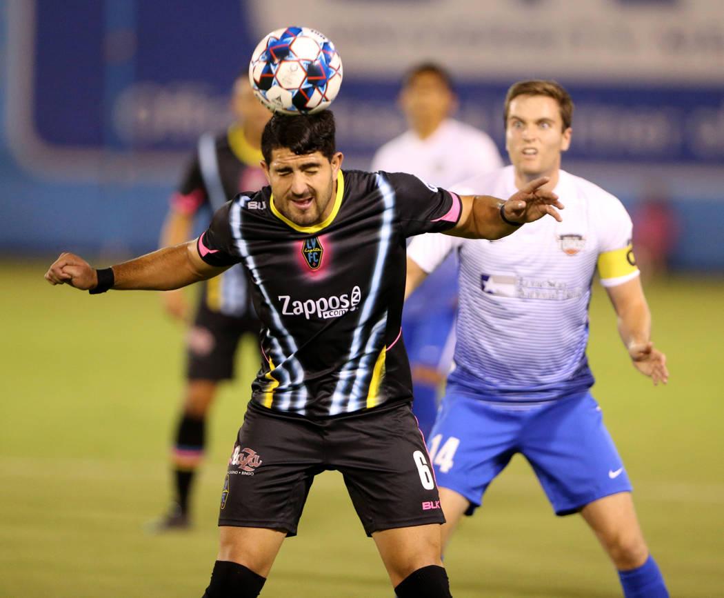 El defensor de Las Vegas Lights FC, Marco Cesar Jaime Jr. (6), cabecea el balón frente al centrocampista del Río Valle FC, Todd Wharton (14), en la primera mitad de un partido de fútbol en Cash ...